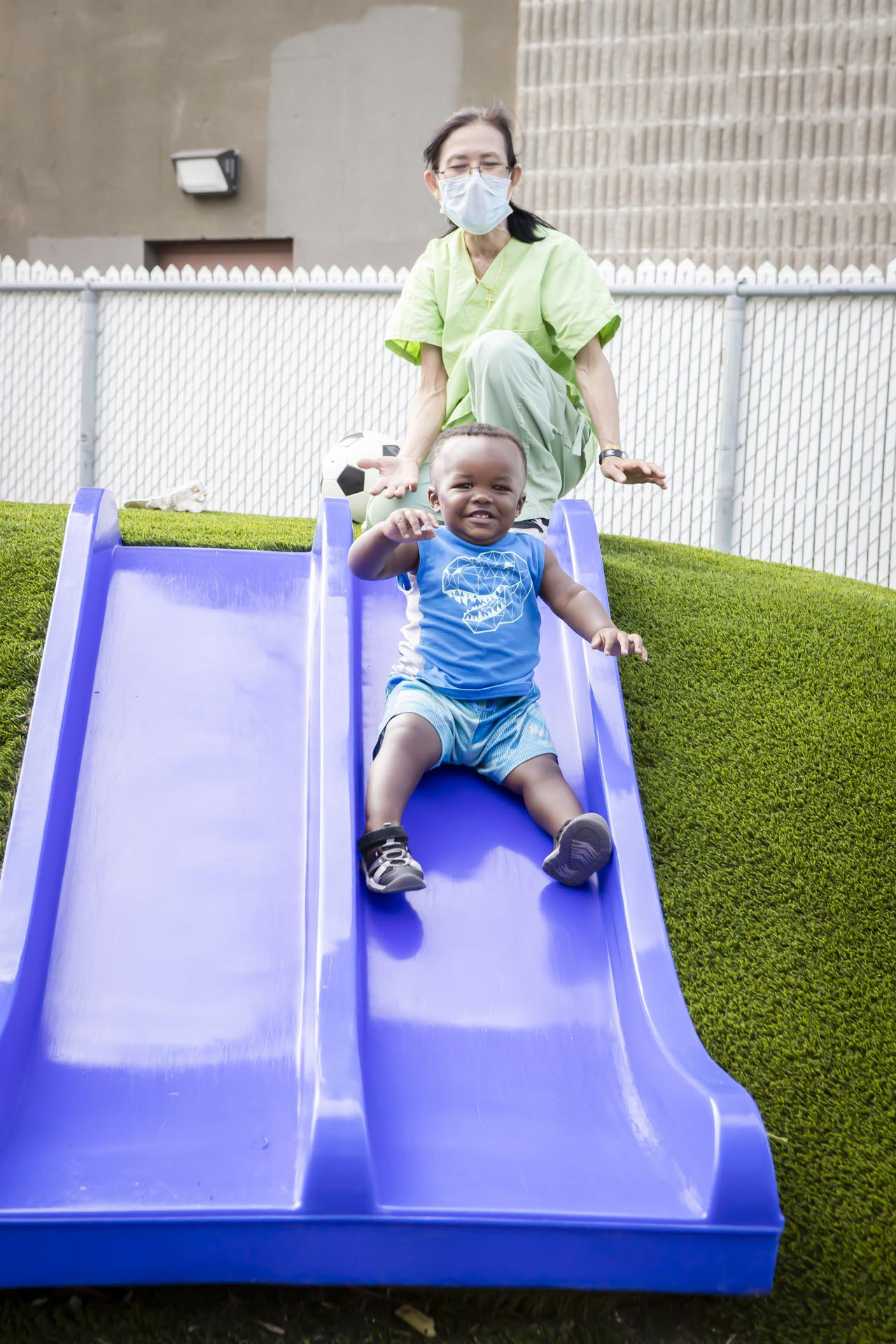 Shot of child and care worker playing on a slide in the Taking Care! outdoor facility