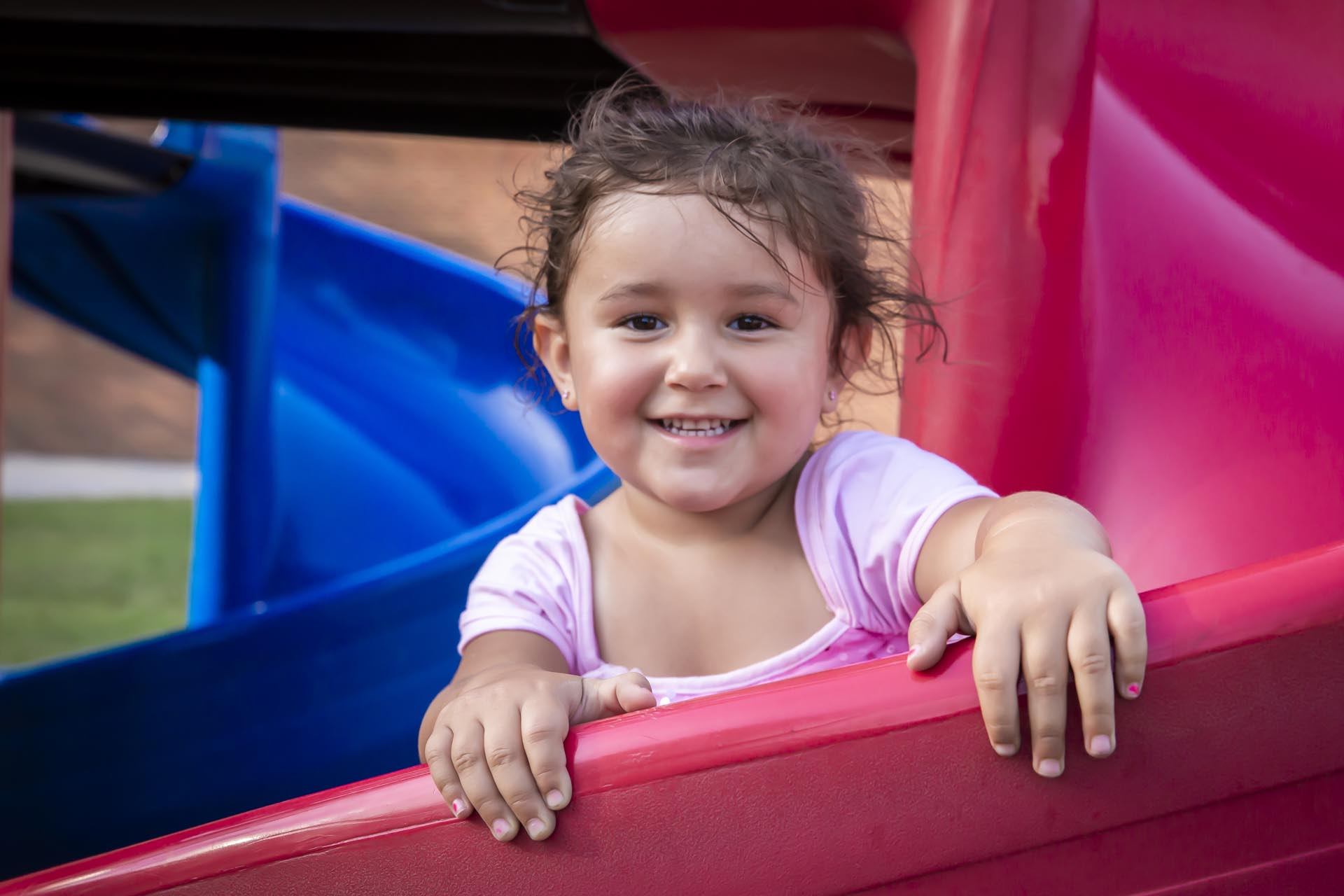 Image of a child on the playground smiling